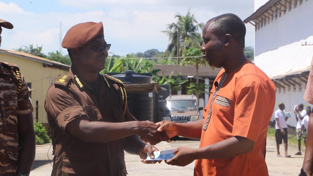 CCF PRESENTS A CHEQUE ON BEHALF OF CHRISTIAN ATSU FOR INMATES TRAINING IN BATIK TIE AND DYE